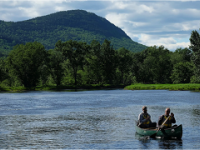 Two people in canoe on a lake with Katahdin in background